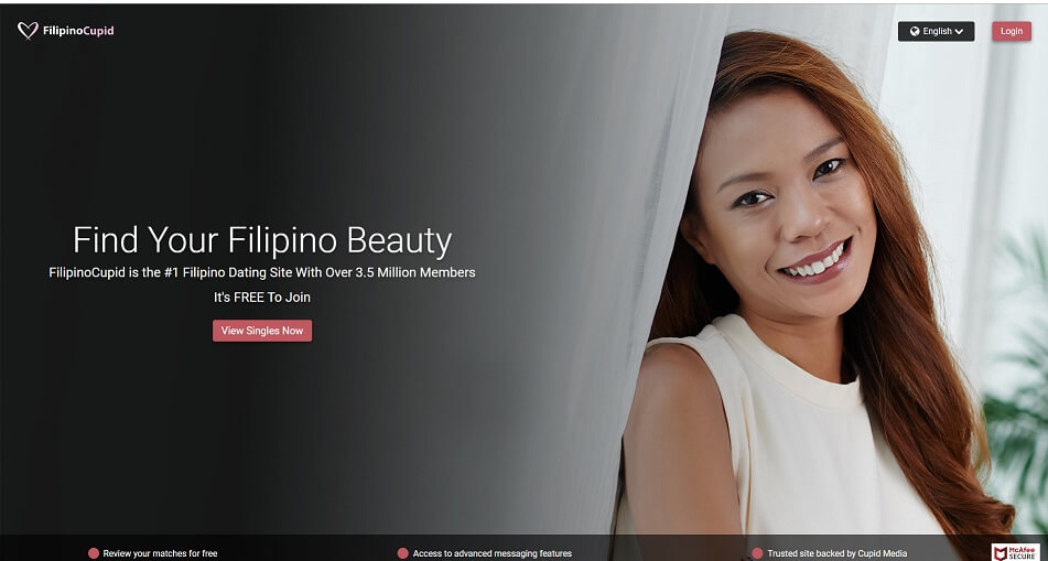 pretty filipina standing by a curtain looking into camera smilingly.
