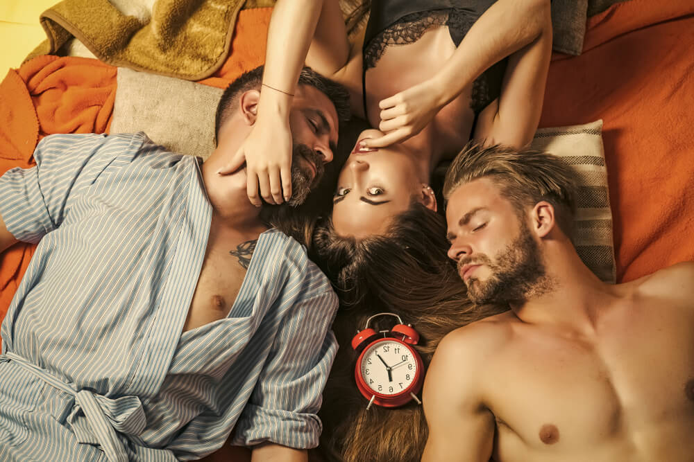 Two sexy men and a hot women lying in bed together, ready for a swinger's night