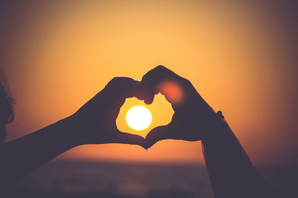 couple forming a heart with their hands while sun goes down