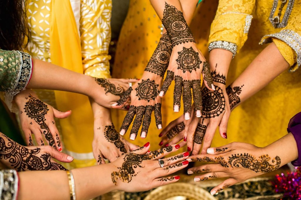 Several hands with henna tattoo on a  muslim marriage wedding