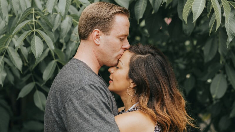man in his mid-fourties gives his attractive girlfriend a forehead kiss