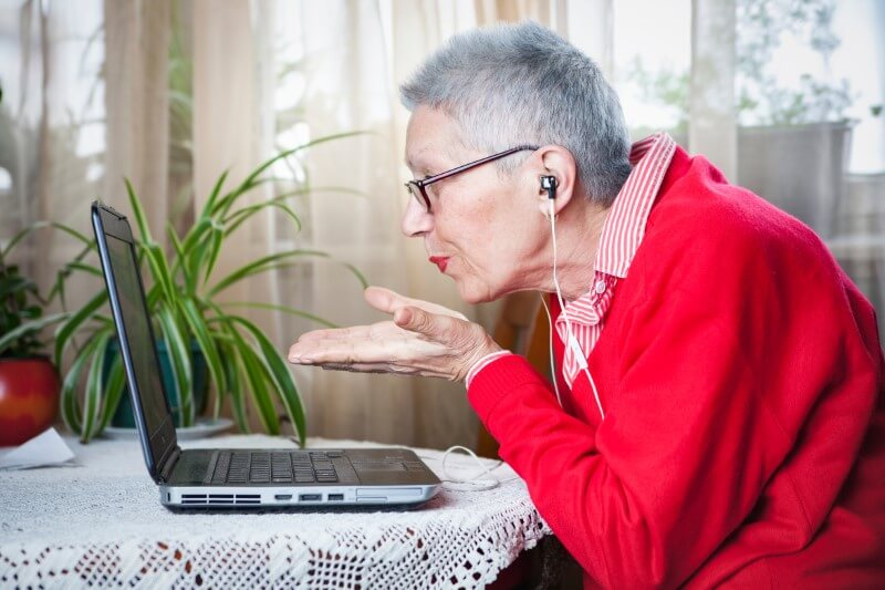 granny dating online blows a kiss to her laptop