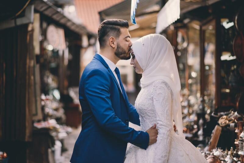 muslim husband kisses his new bride on the forehead