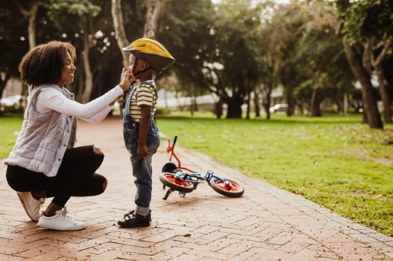 mother helps her son with his helmet while he learns to drive a bike