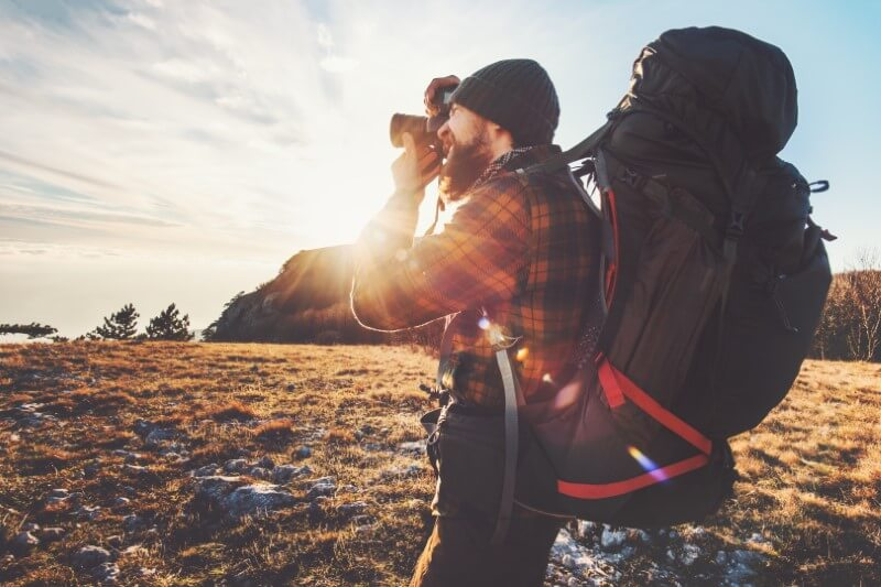 backpacker takes a photo in the sunset