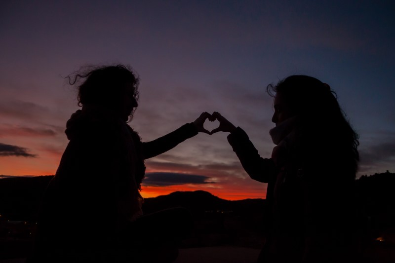 two people forming a heart with their hands in the sunset