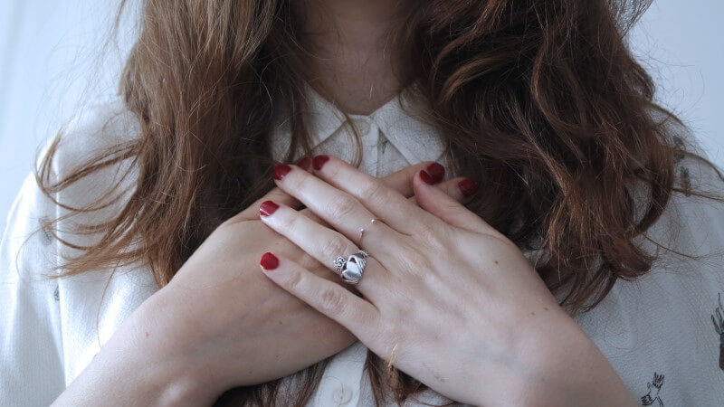 woman holding hands over her heart